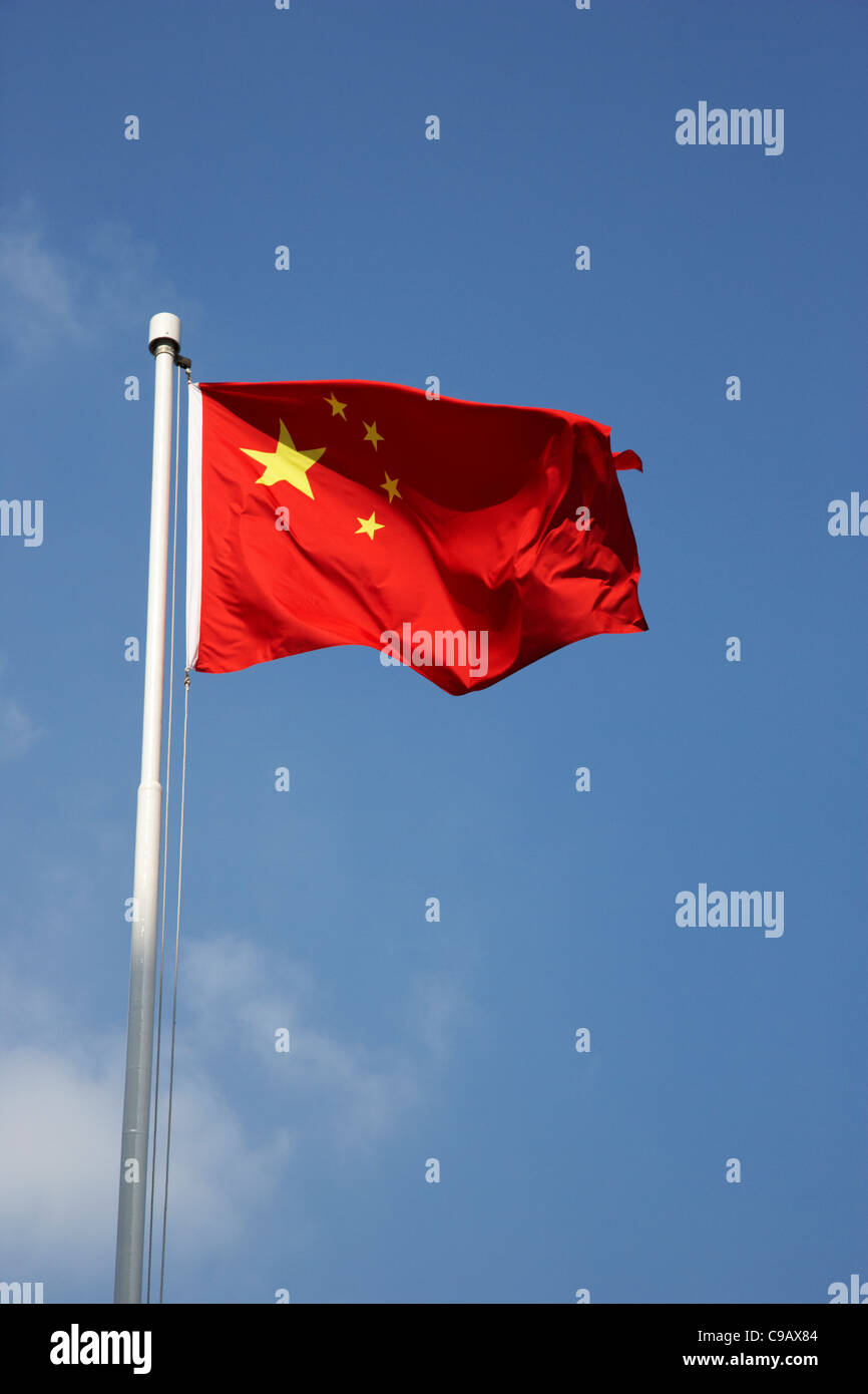 chinese flag flying against a blue sky on a flagpole Stock Photo
