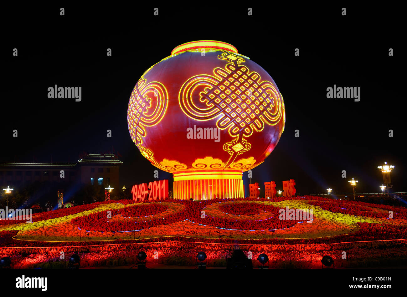Globe and flower decorations at night National Day celebrations in Tiananmen Square with Great Hall of the People - Stock Image
