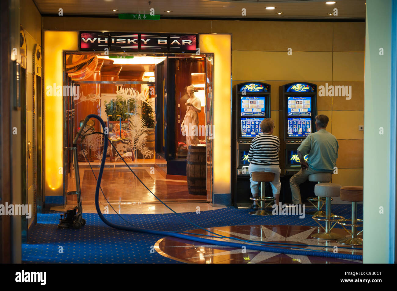 A couple playing slot machines beside a vacuum cleaner on the Cruise ship Birka Paradise casino Stock Photo