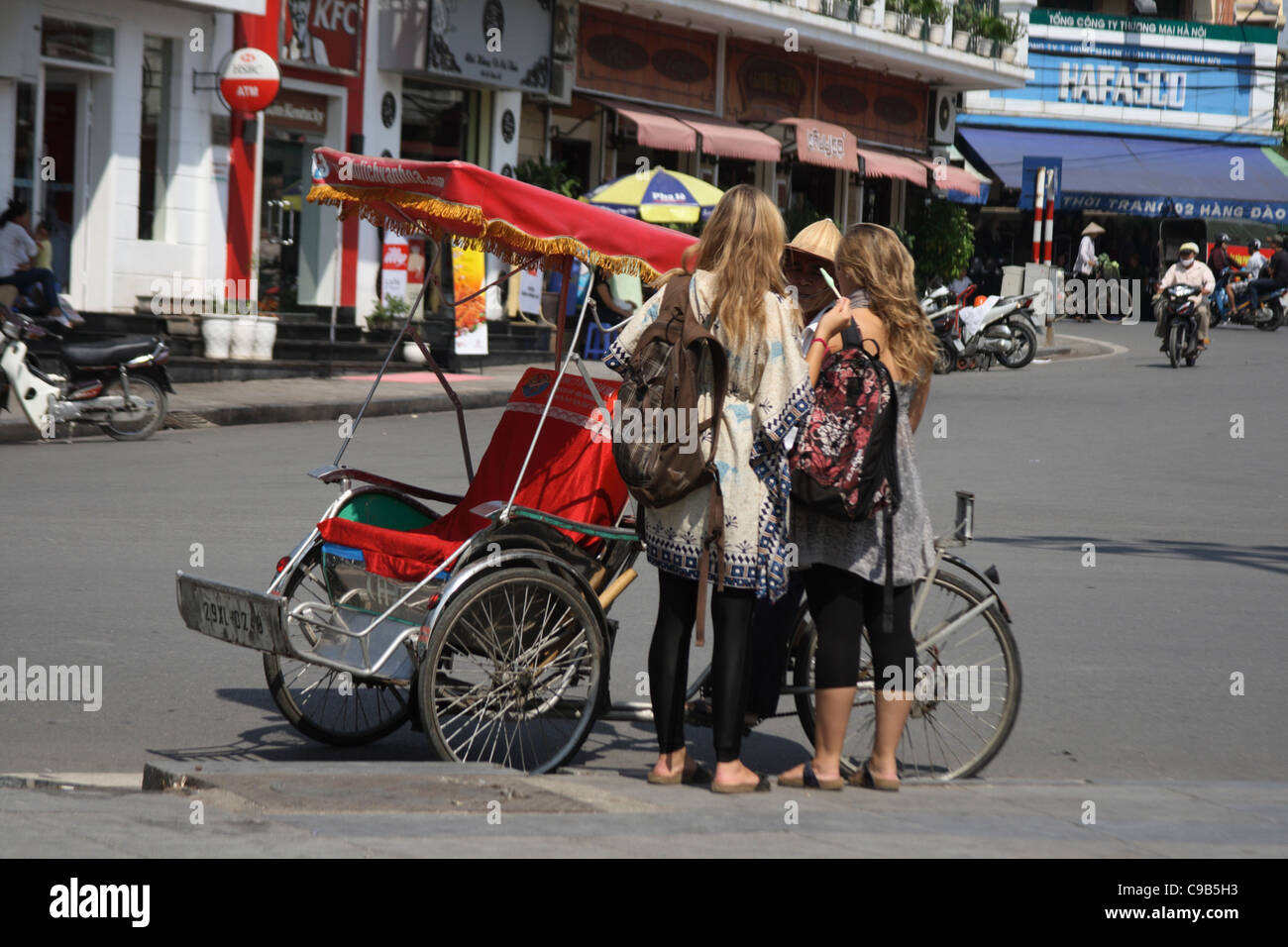tourist negotiating fare with cyclo driver in Hanoi, Vietnam - Stock Image