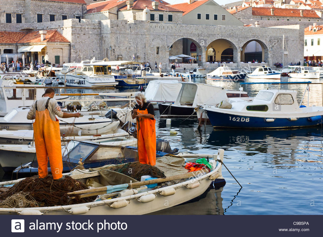 Fishermen preparing nets in the walled city old Dubrovnic, Croatia. Stock Photo