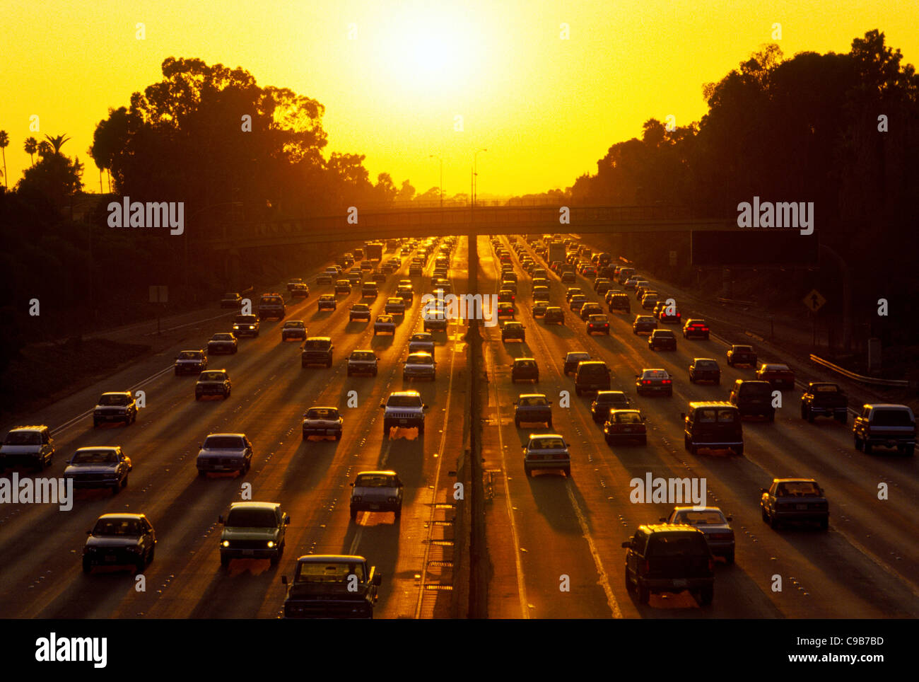 A Los Angeles freeway is crowded with cars and other vehicles as the sun sets during the homebound traffic rush - Stock Image