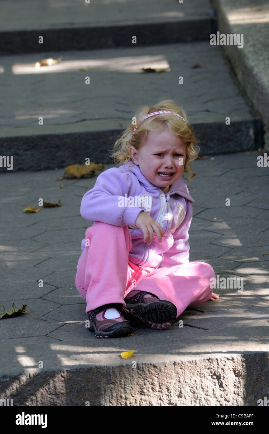 Little girl sitting on the ground and crying having fallen or tripped over - Stock Image