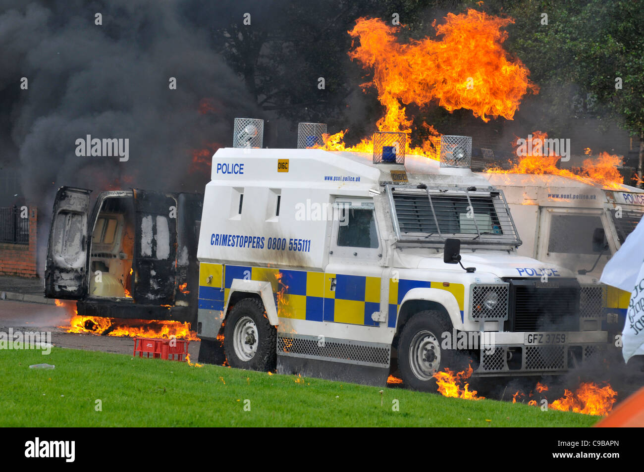 PSNI vehicles set alight by petrol bombs in riots in the Bogside, following a loyalist parade, Londonderry, Northern - Stock Image