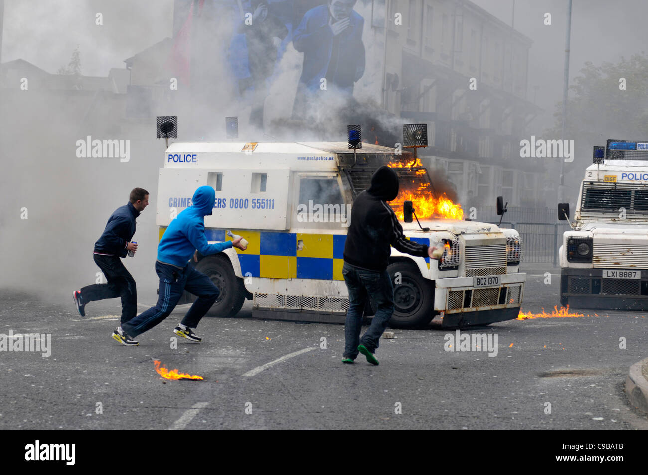 Masked nationalist youths throw petrol bombs at PSNI vehicles during riots in Bogide, Londonderry. - Stock Image
