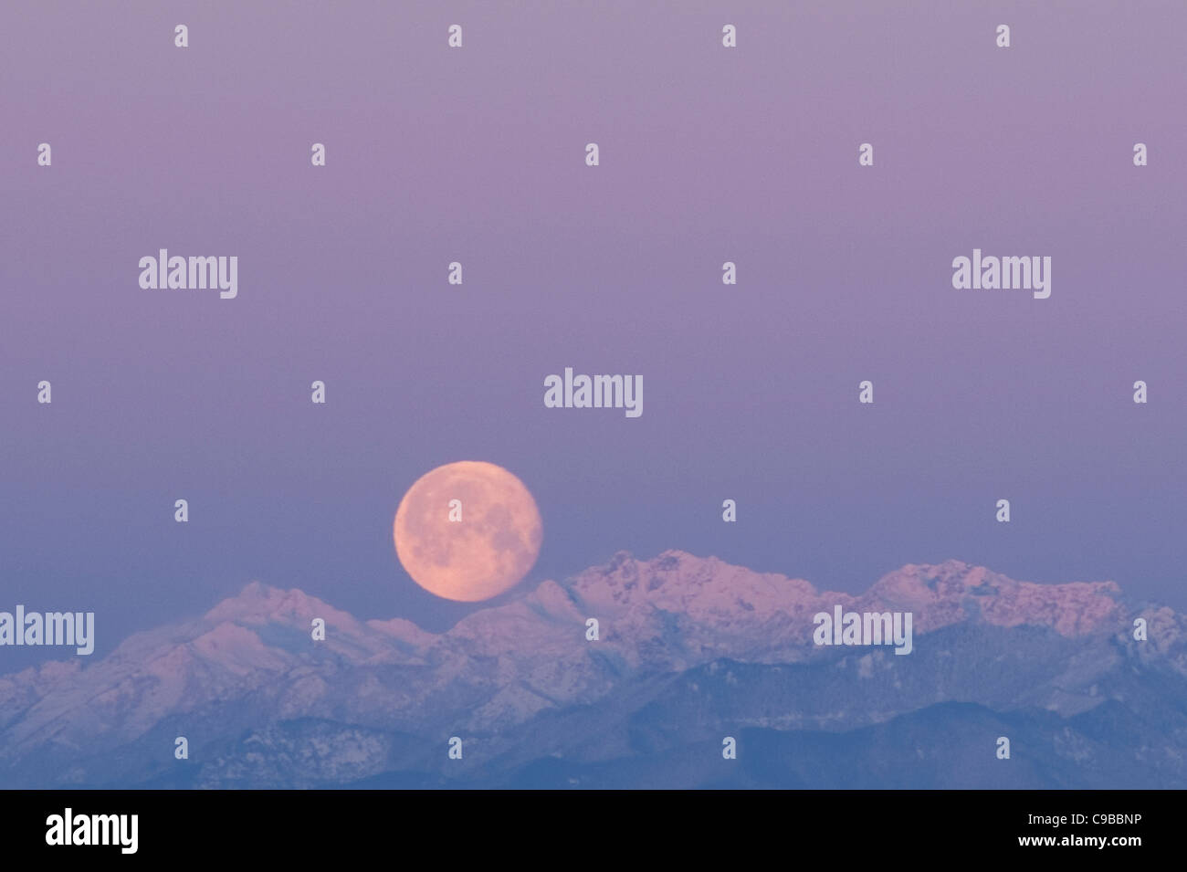 Sunrise with moon set over snow covered Olympic Mountains - Stock Image