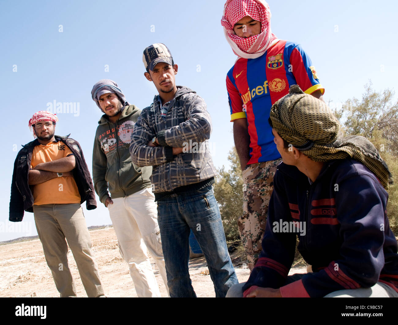 A group of young men, unemployed Middle Eastern day-labourers, waiting for work on the outskirts of al Azraq Oasis Stock Photo