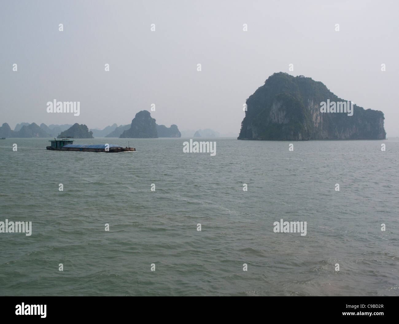 Cargo boat passing Halong Bay rock formations in the South China Sea, Vietnam - Stock Image