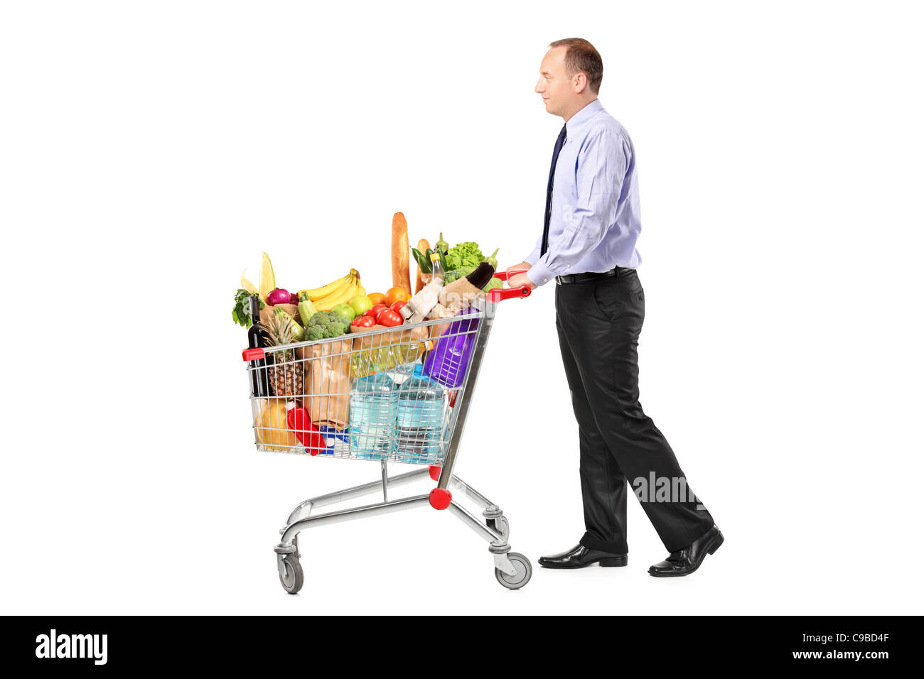 Person pushing a shopping cart full with groceries - Stock Image