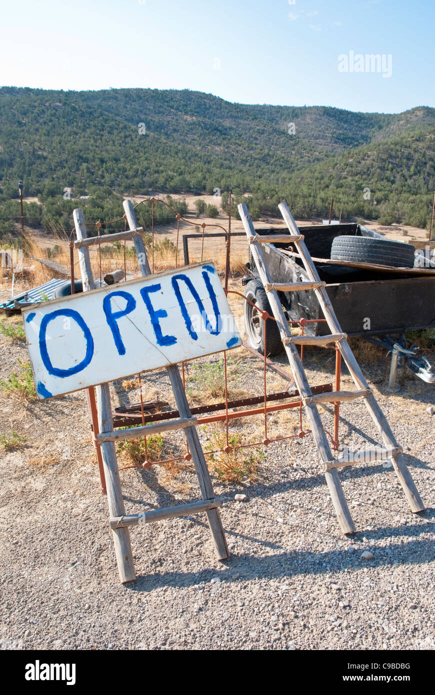 'OPEN' says the sign at a roadside junk shop along route 70 in southern New Mexico. - Stock Image