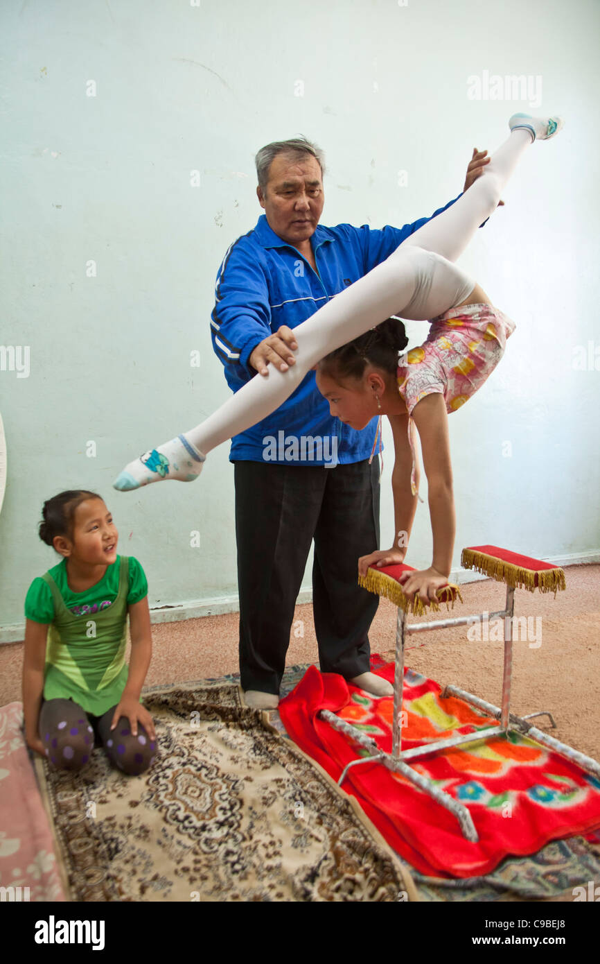 Contortionist coach in Mongolia with two of his young students. - Stock Image
