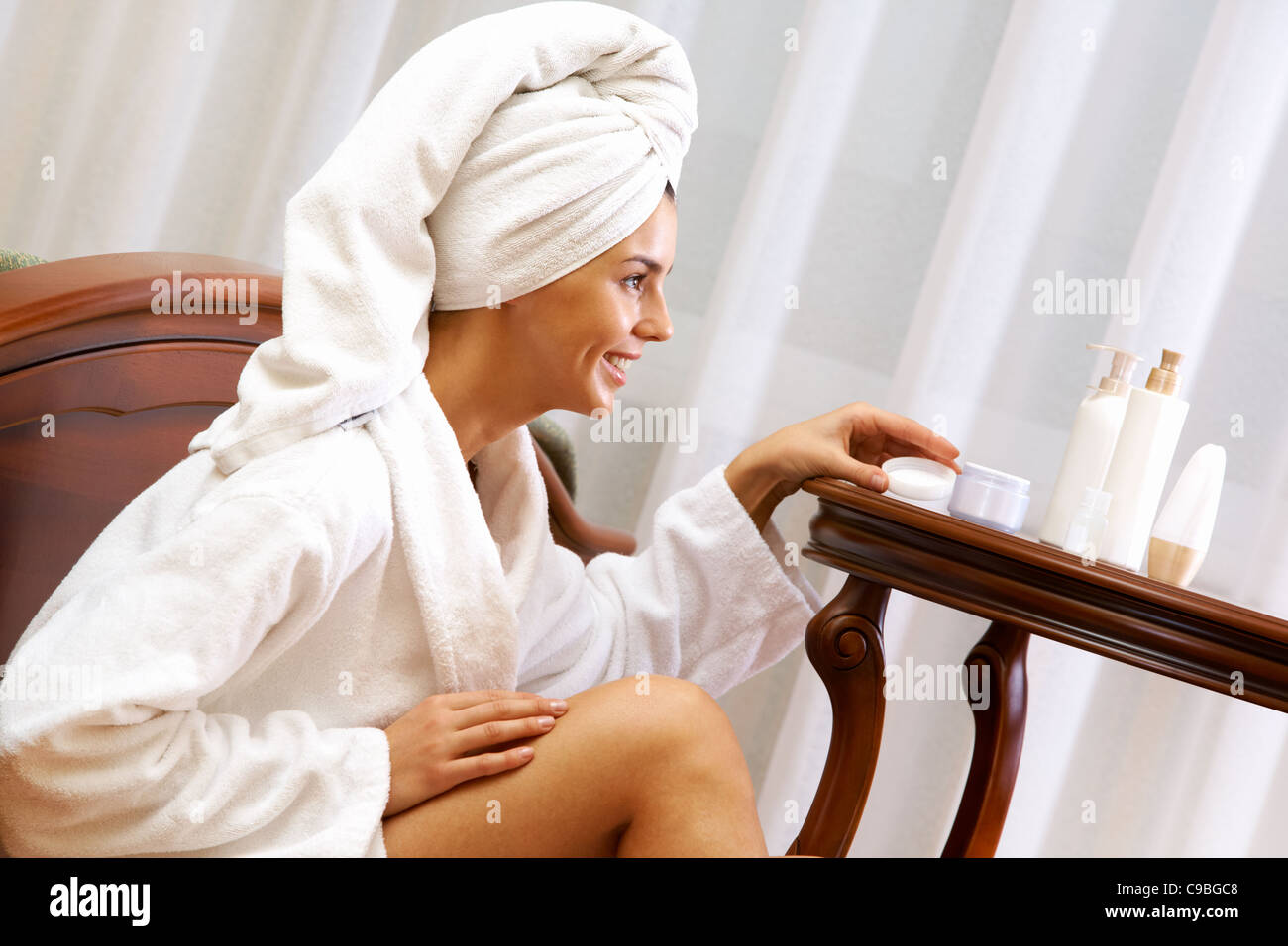Portrait of pretty female taking care of her skin after bath - Stock Image