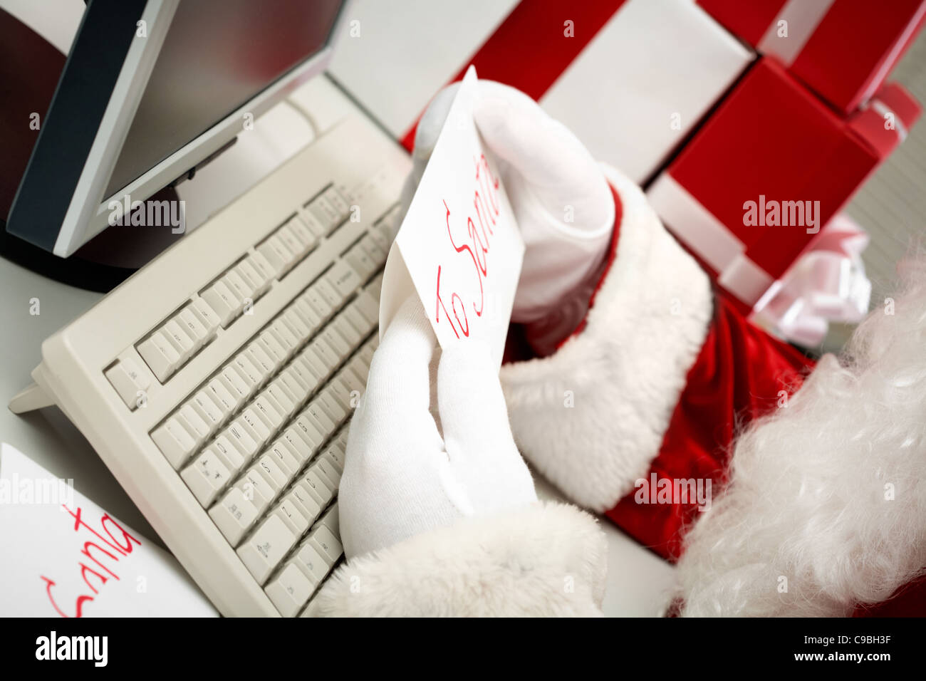 Close-up of Santa gloved hands holding letter with note 'To Santa' - Stock Image