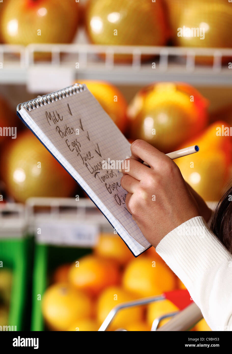 Image of female hands with pen holding product list while buying goods in supermarket - Stock Image