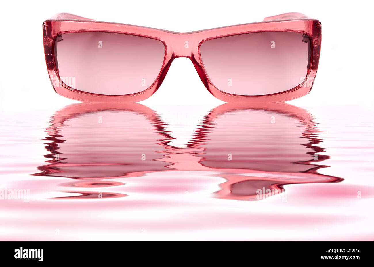 4d4225d1b5d2d1 A pair of pink ladies sunglasses isolated on a white background and  reflecting in water ripples
