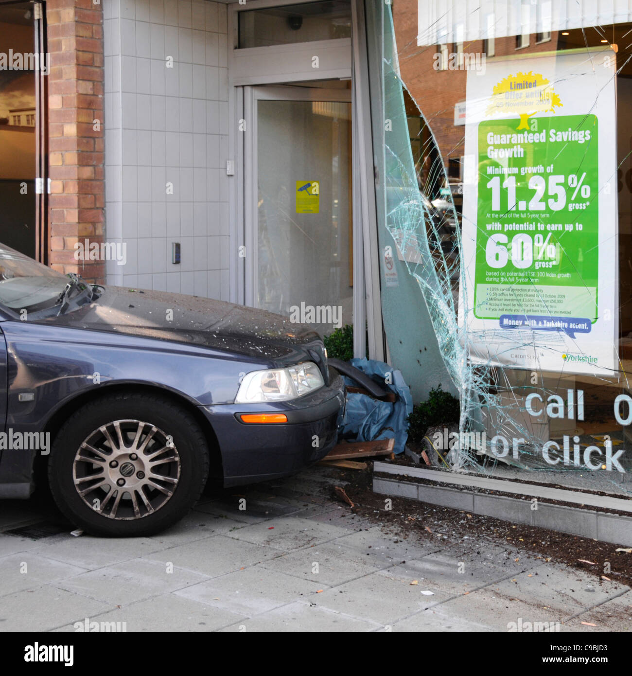 Road traffic accident crash car mounts pavement in shopping street scene & hits window of building society shop Stock Photo