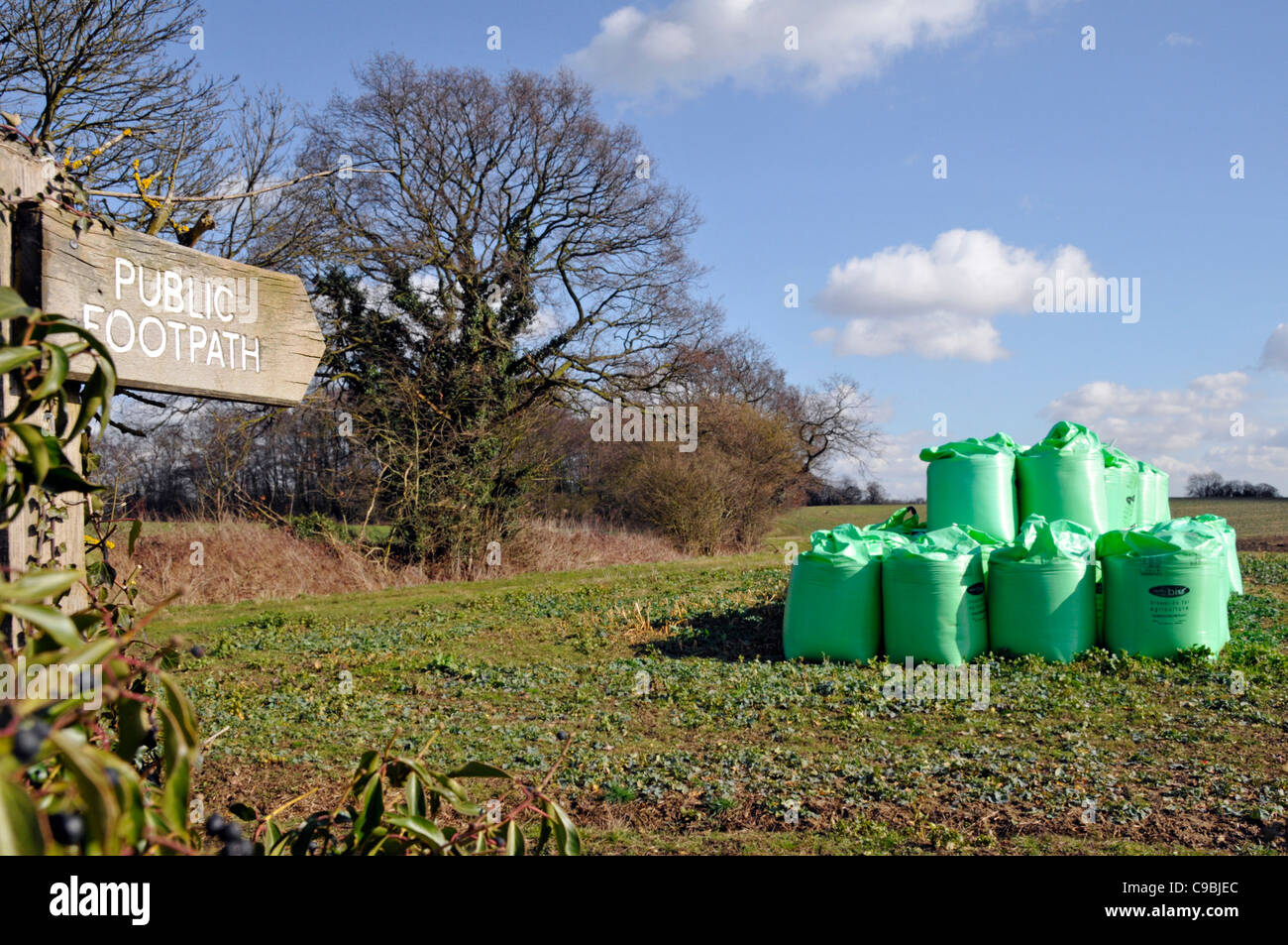 Public Footpath sign and bagged Biosolids contents derived from sewage by Nutri Bio part of Anglian Water stacked Stock Photo