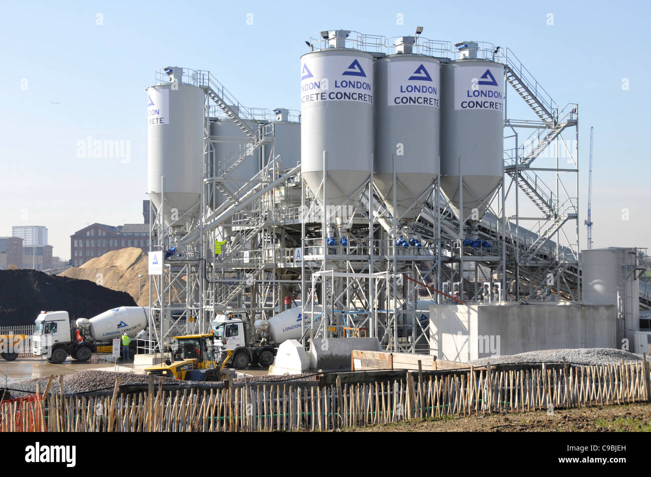 London Concrete industrial site distribution depot with cement silos aggregate storage & mixer delivery lorry - Stock Image