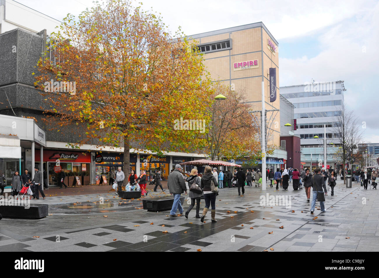 Autumn street scene people walking along town centre retail shopping high street with Queensmere shoppers centre - Stock Image