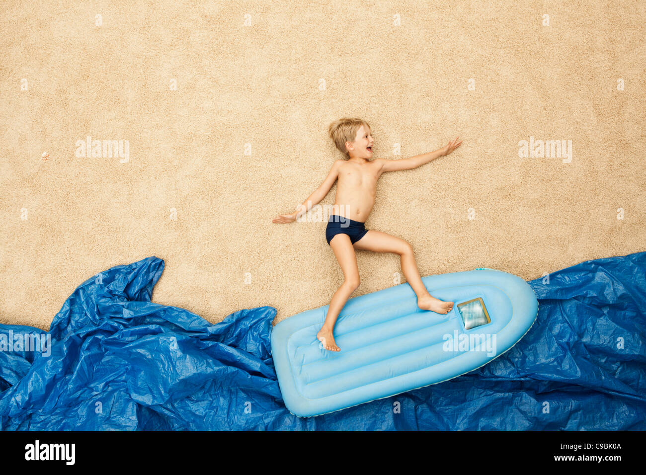 Germany, Boy on inflatable raft in water at beach - Stock Image