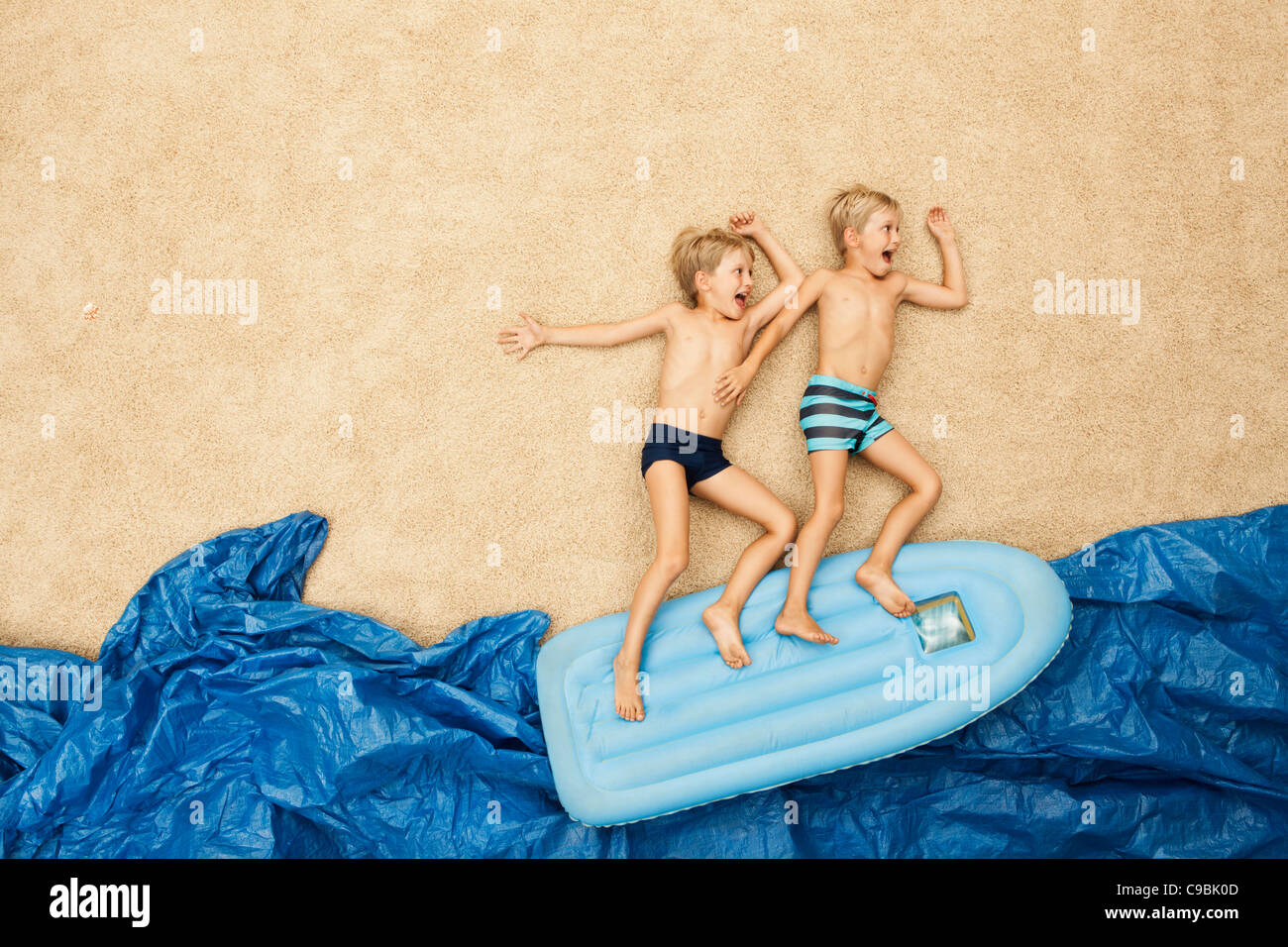 Germany, Boys on inflatable raft in water at beach Stock Photo
