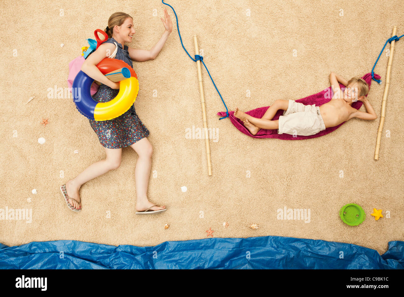 Germany, Mother with toys and son resting in hammock at beach - Stock Image