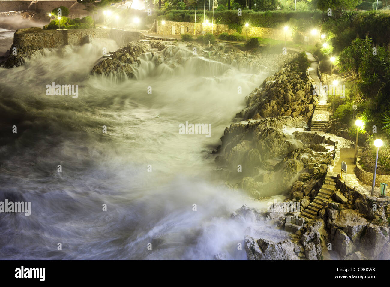 ROUGH SEA 1.3-seconde night time exposure of a rough sea on the rocky shoreline in the city of Nice, French Riviera, Stock Photo