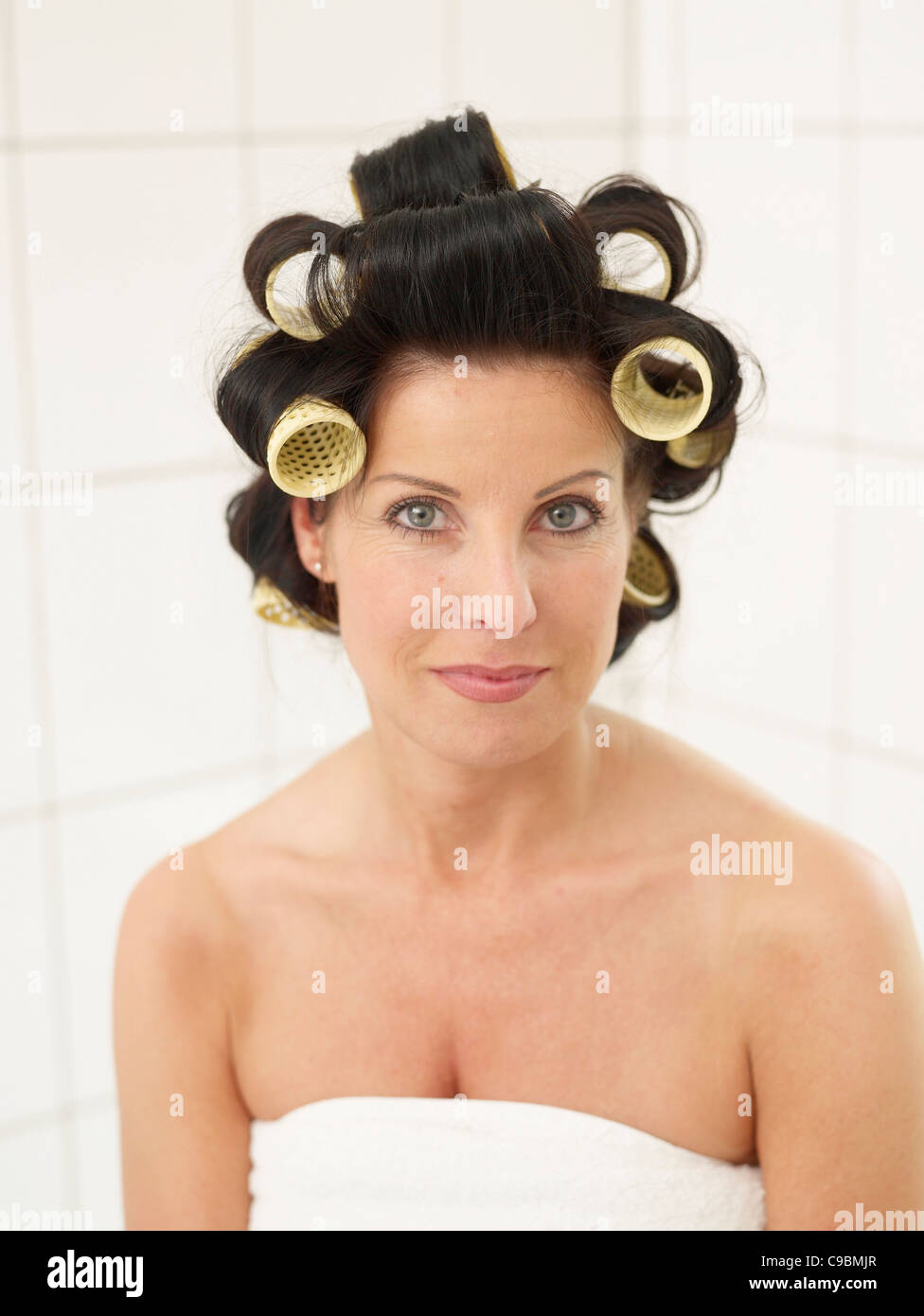 Mature woman in towel with hair rollers, smiling, portrait - Stock Image