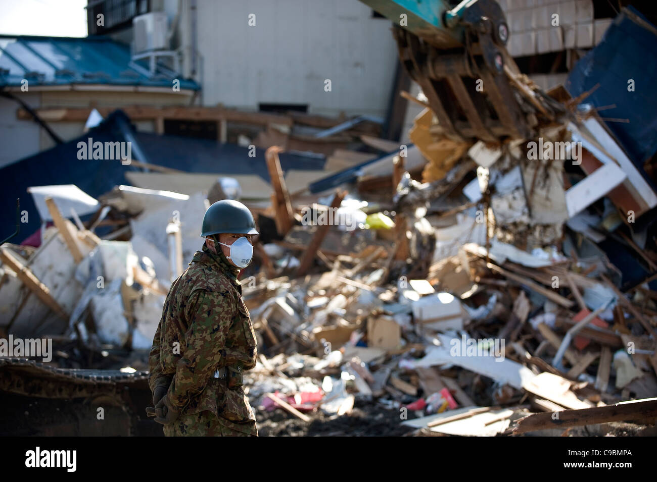 A Japan Self Defense Force member looks on as a fork lift truck clears debris from the streets in Tona, Miyagi Prefecture, - Stock Image