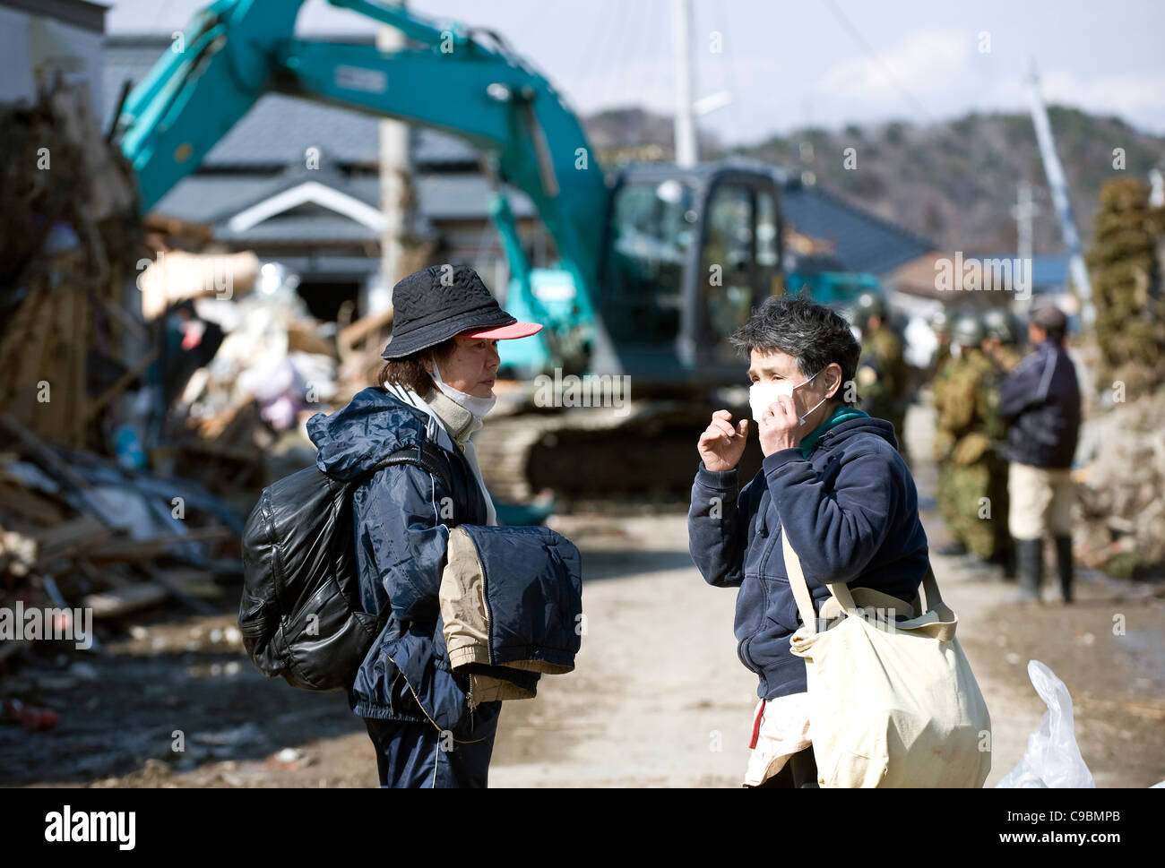 Two residents share their experiences of the March 11 quake and tsunamis as a fork lift truck clears debris from - Stock Image