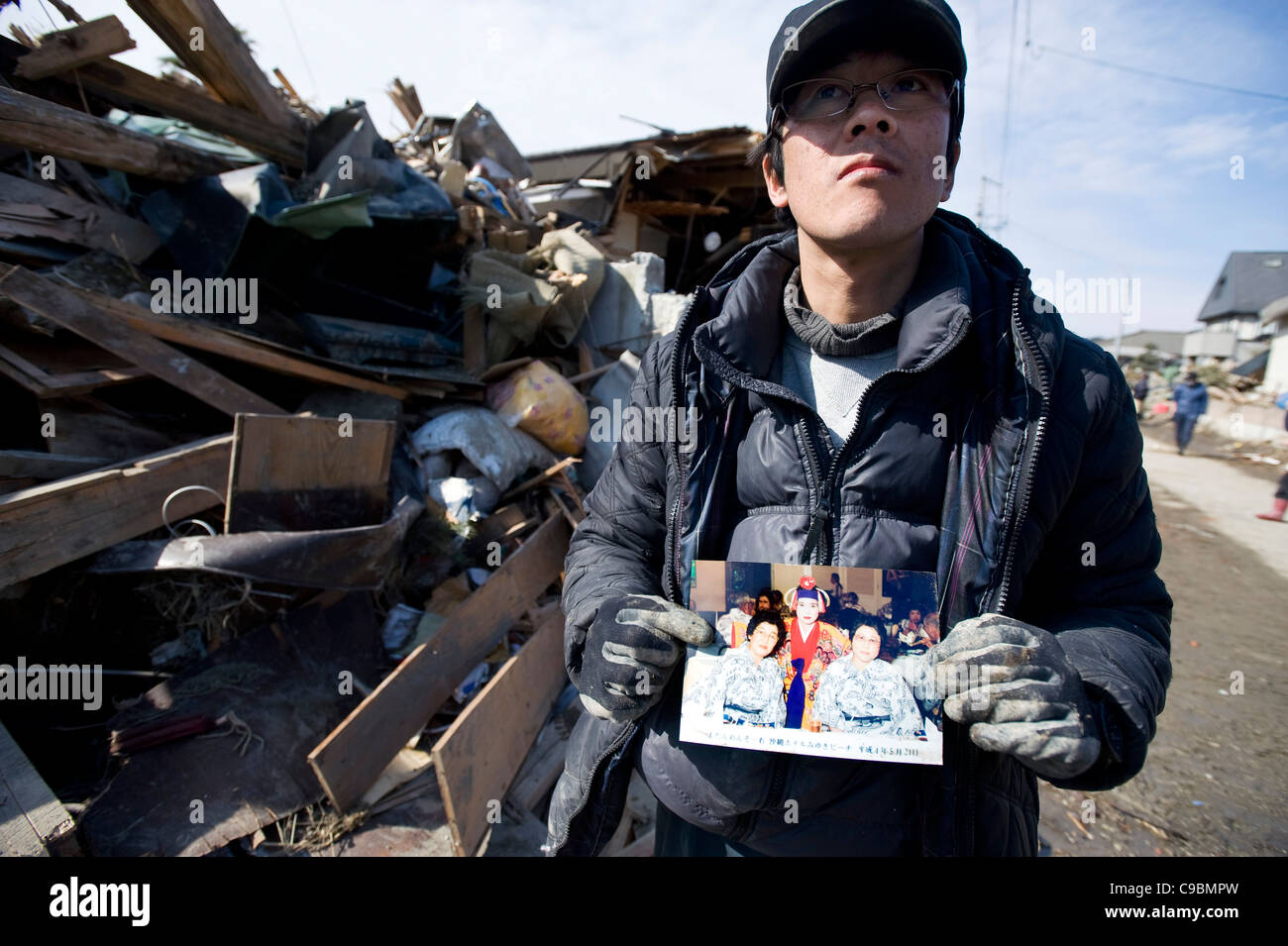 Makoto Takahashi shows a photo of his mother (shown on the left of the photo) whom he found dead outside their home - Stock Image
