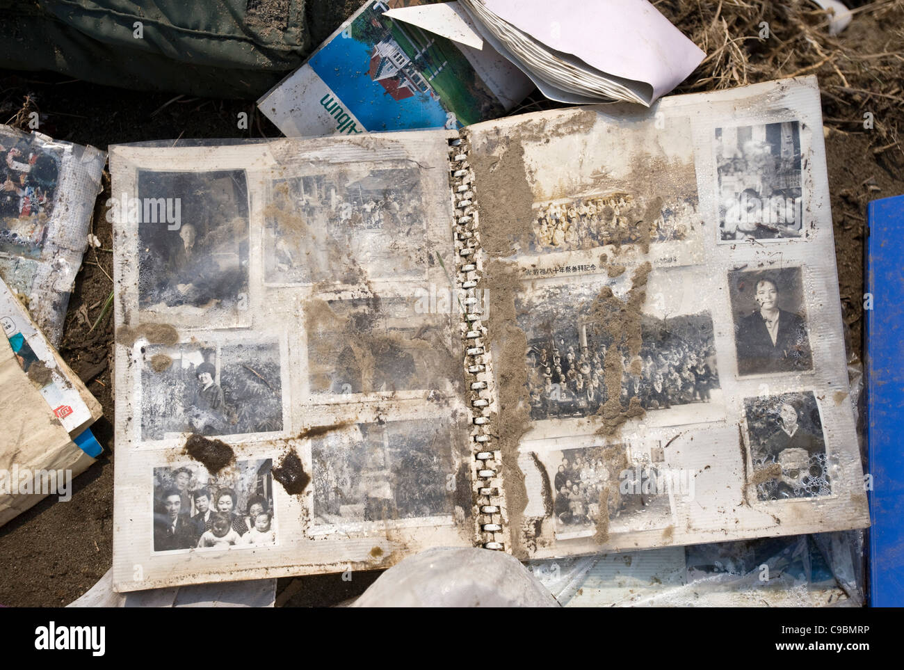 A photo album lies among the rubble of Nobiru, Miyagi Prefecture, Japan - Stock Image
