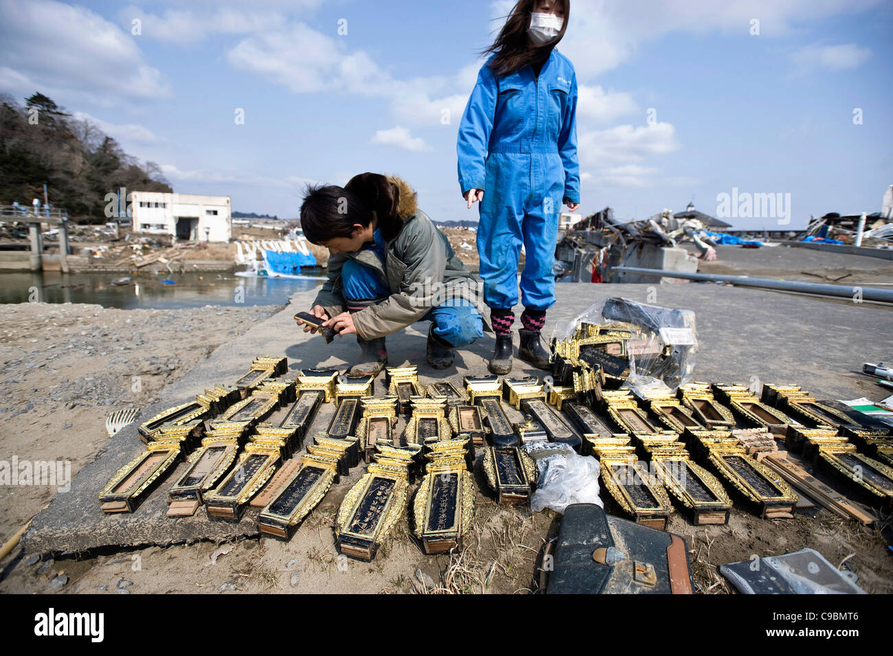Kenji Onodera (35) and his wife Hiromi (40), look at items salvaged from a temple badly damaged by the March  tsunami - Stock Image