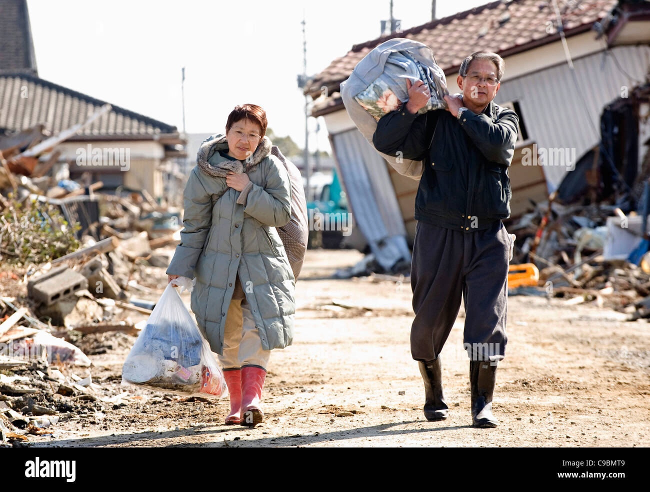 Yoshio Isawa, 60 (R) and his wife Makiko carry personal belongings rescued from their battered home in Tona, Miyagi - Stock Image