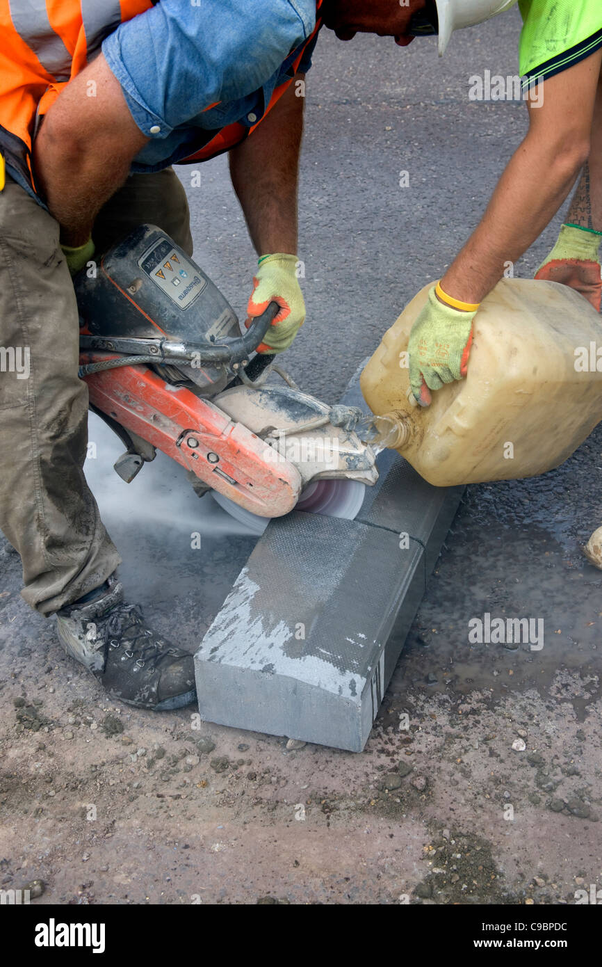 Workmen cutting a curb-stone, Kerb-stone, with a diamond tipped cutter, using water to keep disc cool. - Stock Image