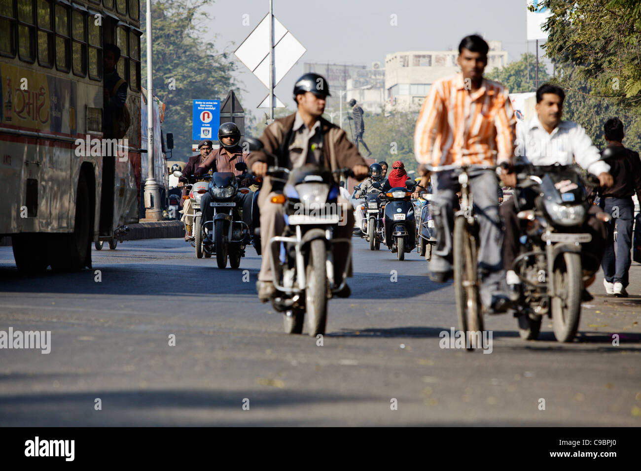 Traffic in Ahmedabad, Gujarat state, India. Statue of Mohandas Gandhi on background. - Stock Image