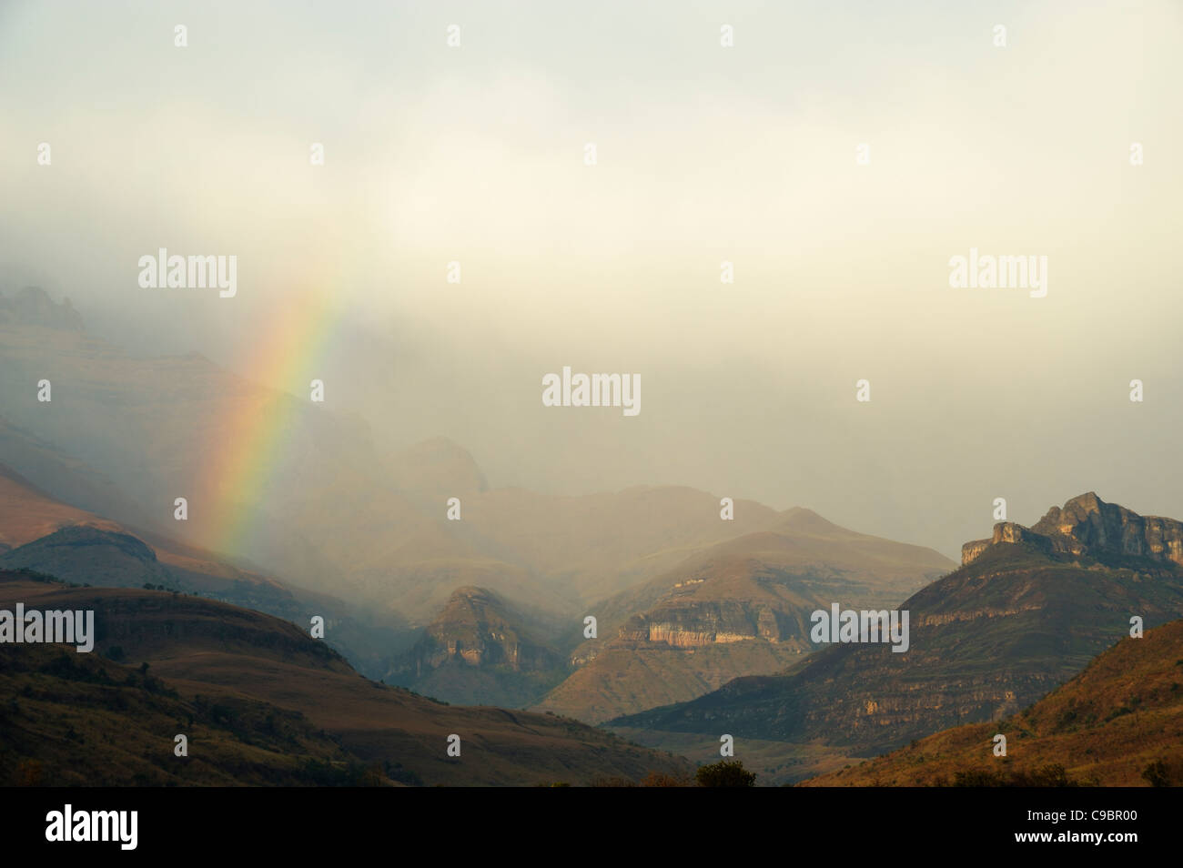 Rainbow at the base of the Amphitheatre range in the Drakensberg Mountains, Royal Natal, Kwazulu-Natal, South Africa Stock Photo