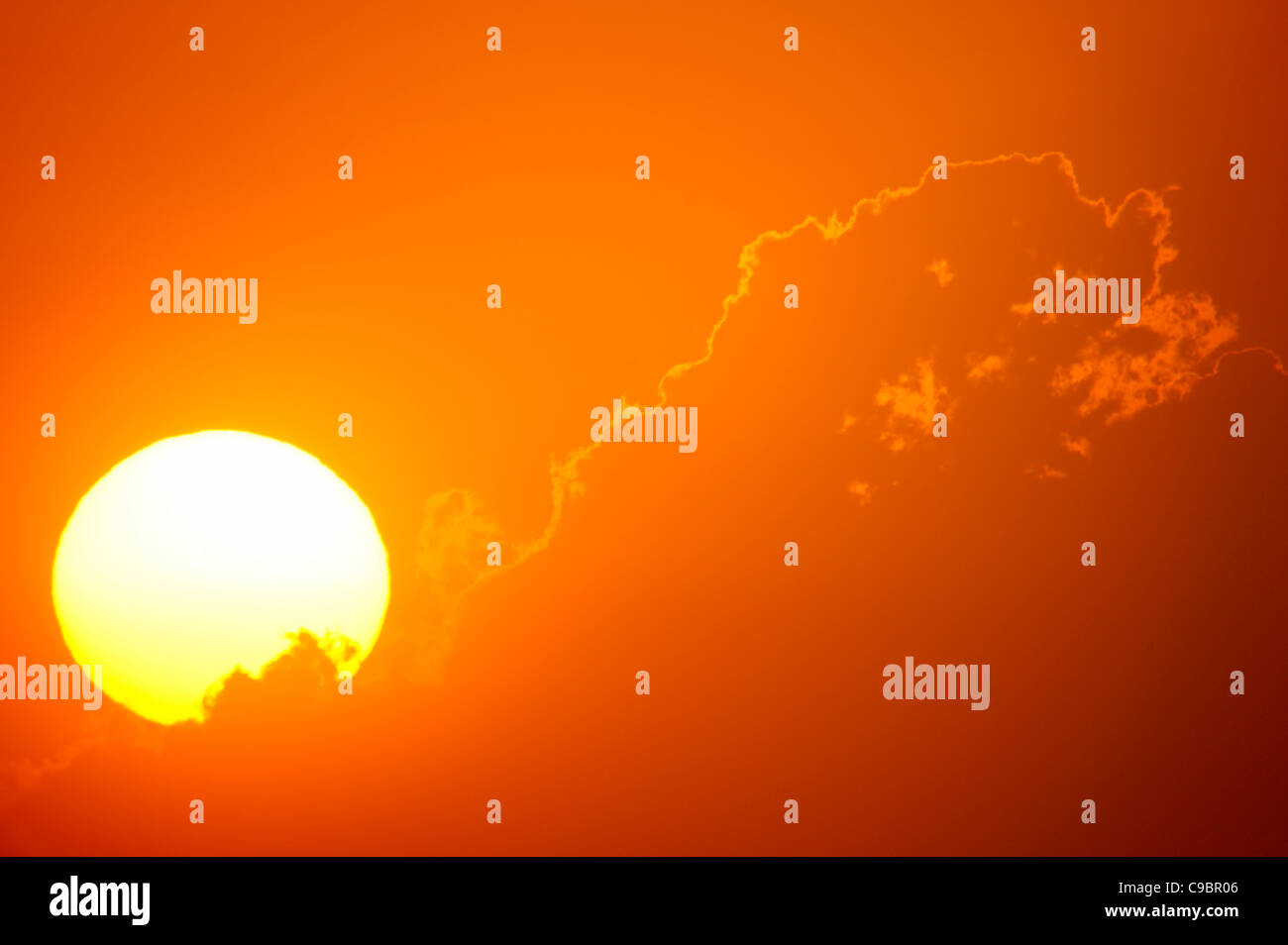 Telephoto view of the rising sun behind orange clouds, Durban, Kwazulu-Natal, South Africa - Stock Image