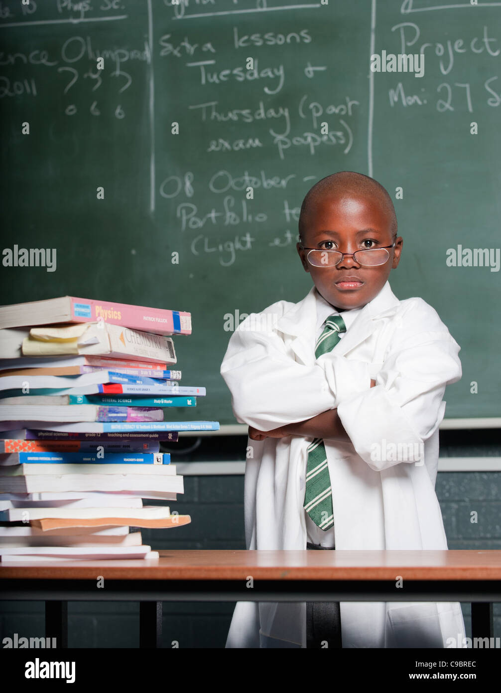 Portrait of boy wearing lab coat in classroom, Johannesburg, Gauteng Province, South Africa - Stock Image