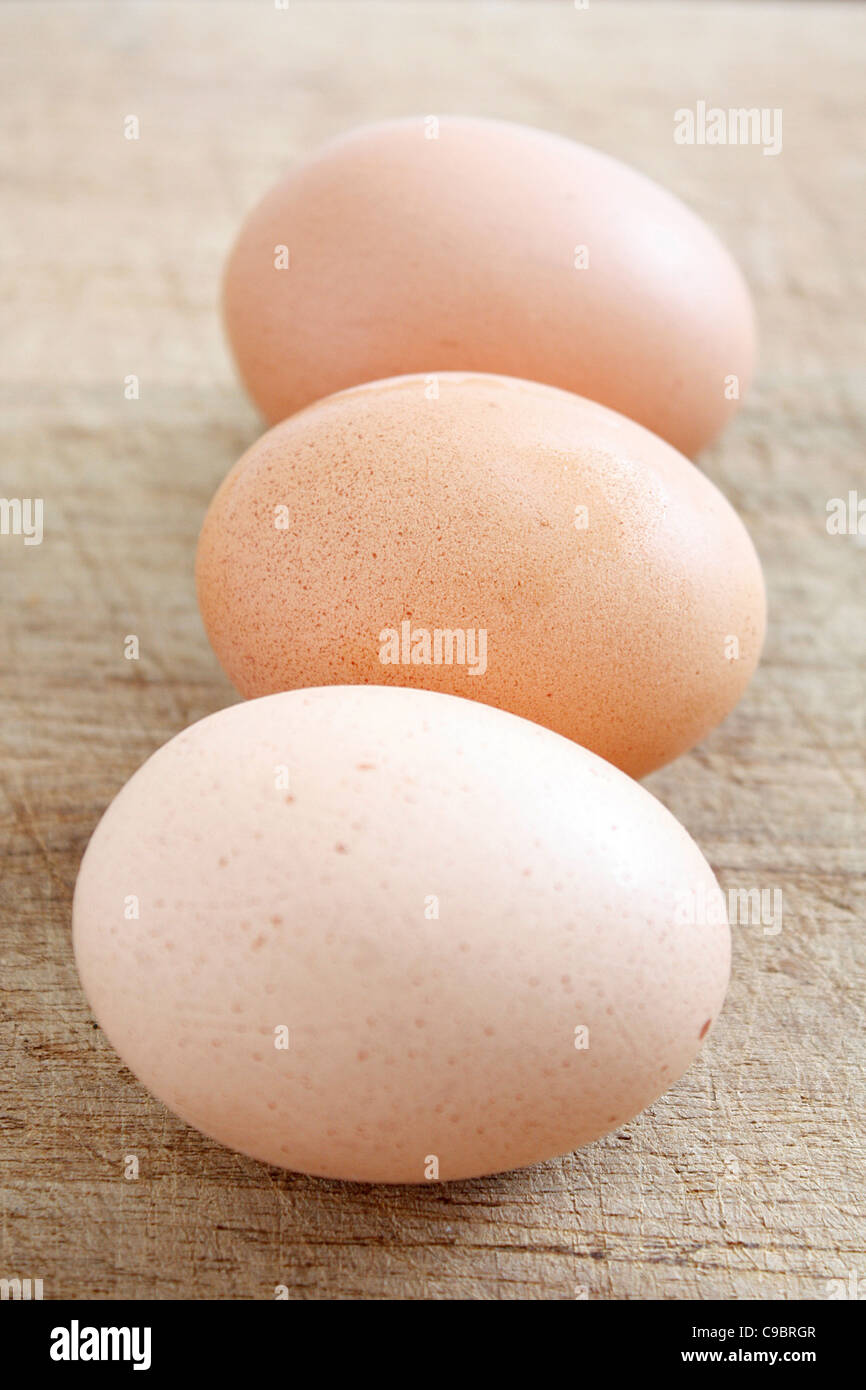 Eggs on a wooden surface - Stock Image