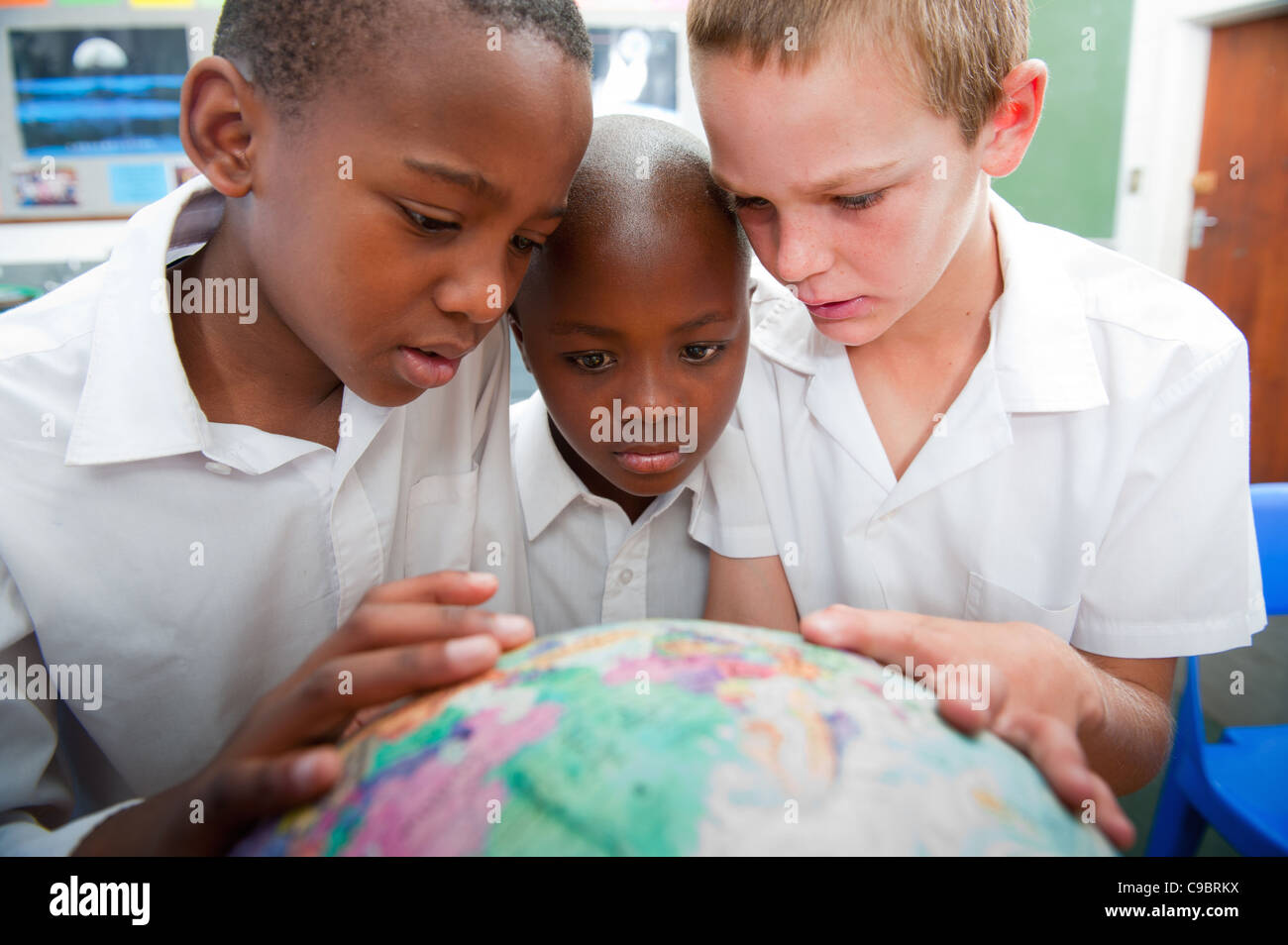 Three boys looking at globe in classroom, Johannesburg, Gauteng Province, South Africa - Stock Image