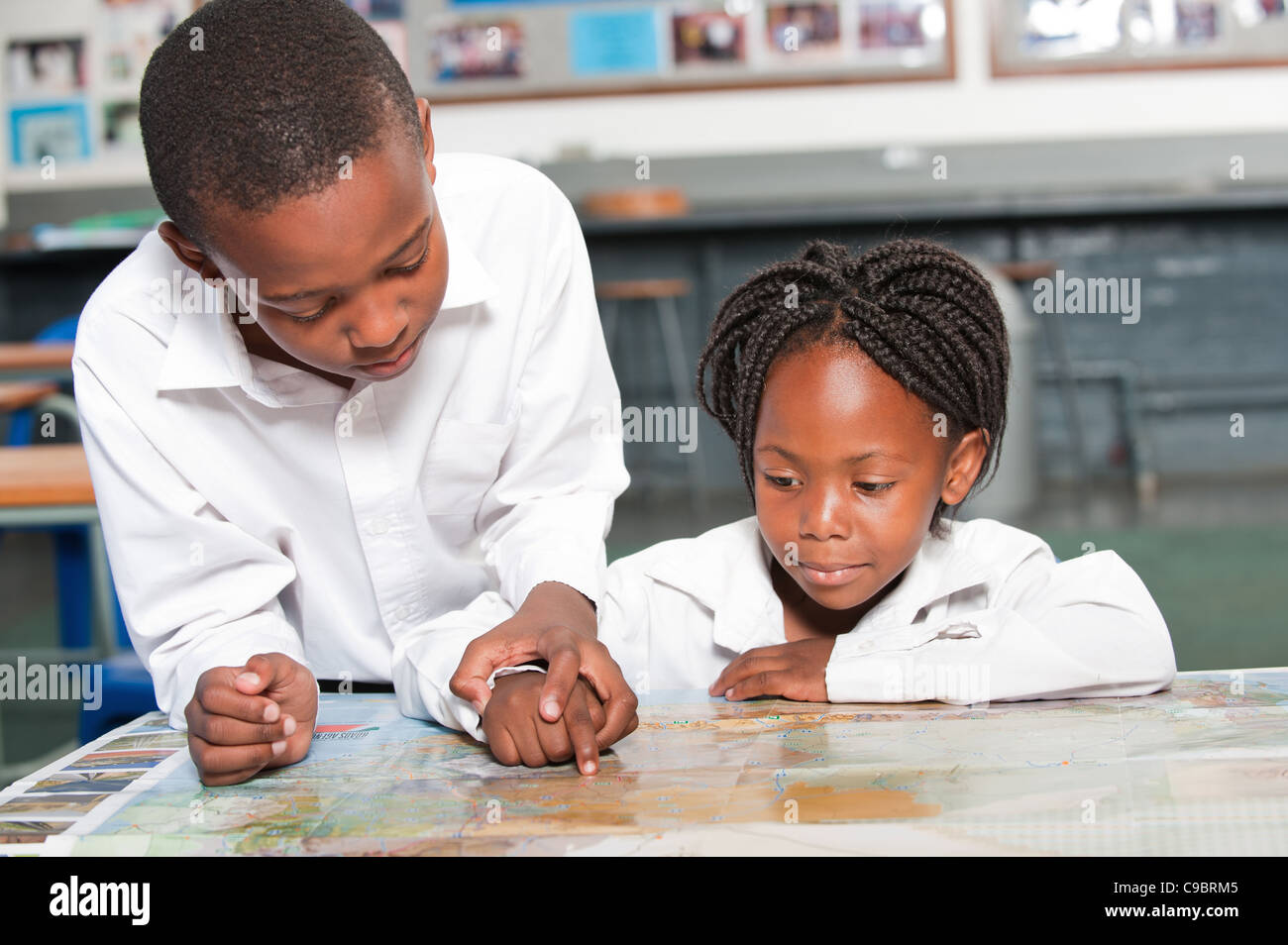 Boy and girl observing world map in classroom, Johannesburg, Gauteng Province, South Africa - Stock Image