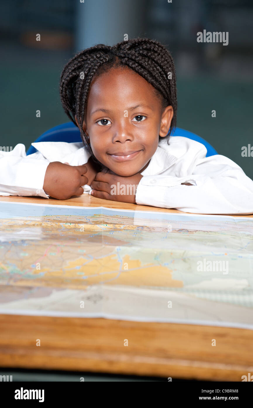 Portrait of girl sitting at desk with world map in classroom, Johannesburg, Gauteng Province, South Africa - Stock Image
