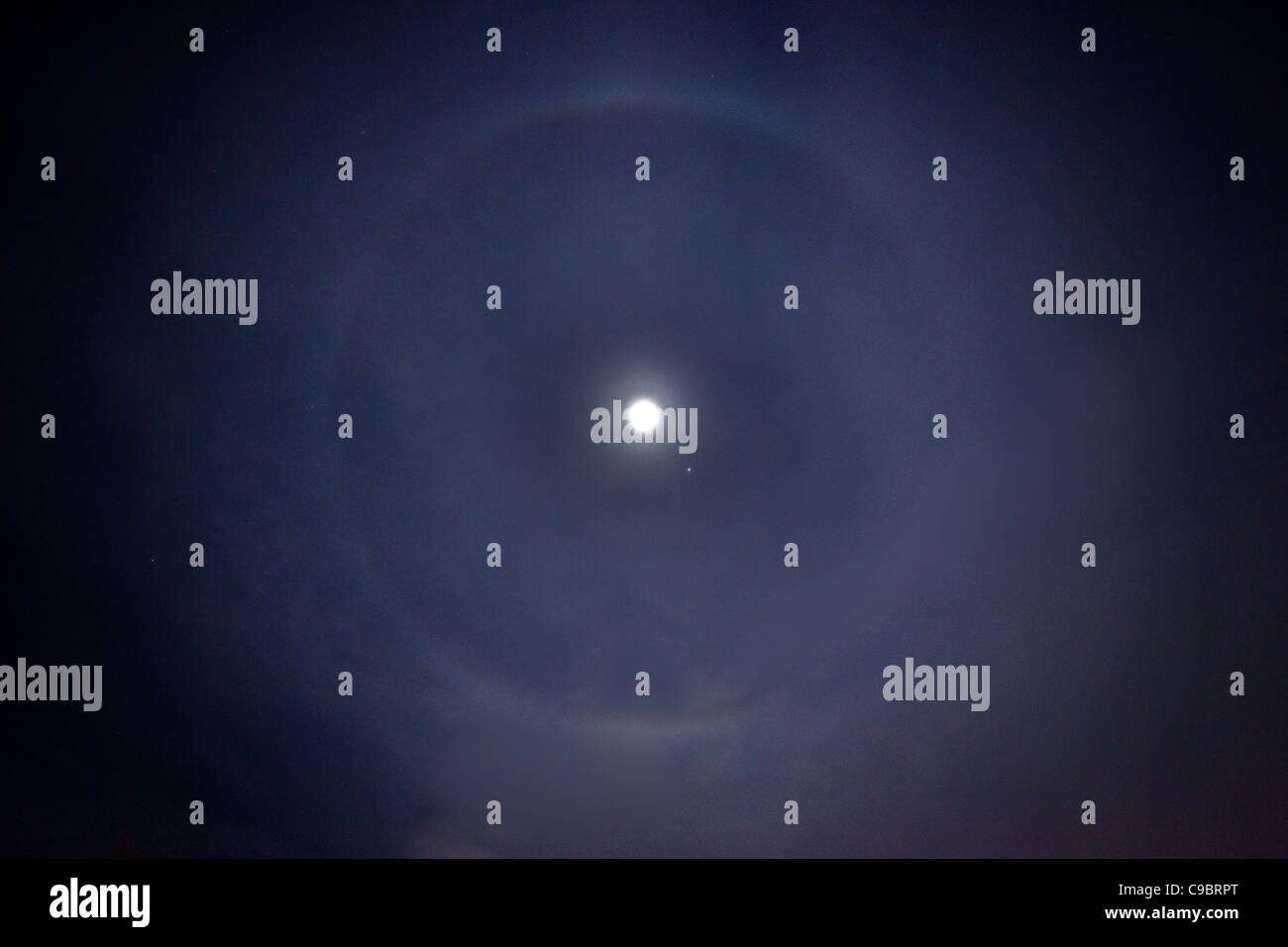 Moon ring phenomenon where a whitish halo surrounds the moon in winter. - Stock Image
