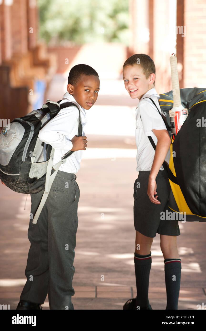 Portrait of two boys walking down school corridor, Johannesburg, Gauteng Province, South Africa - Stock Image