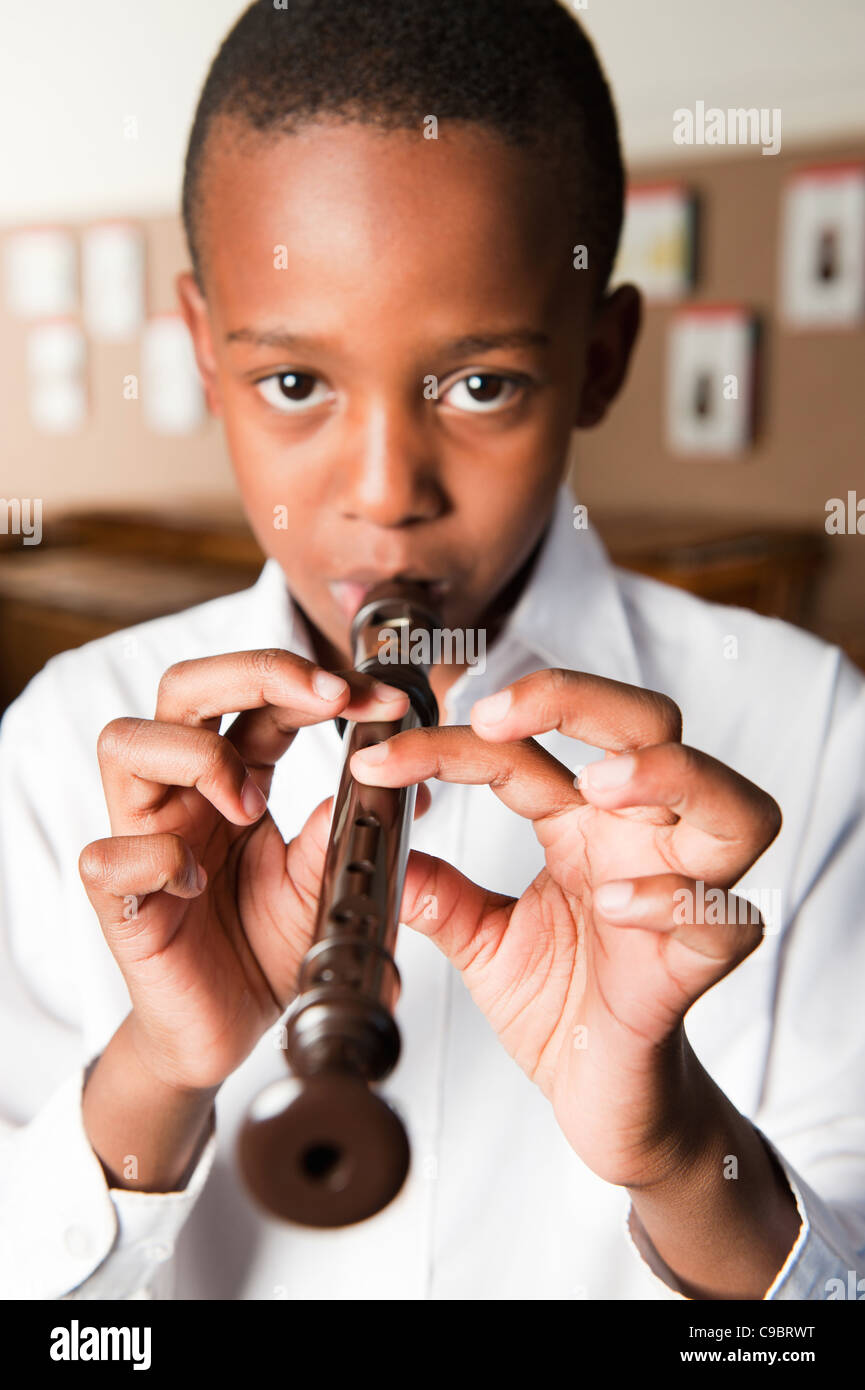 Portrait of boy playing recorder in classroom, Johannesburg, Gauteng Province, South Africa - Stock Image