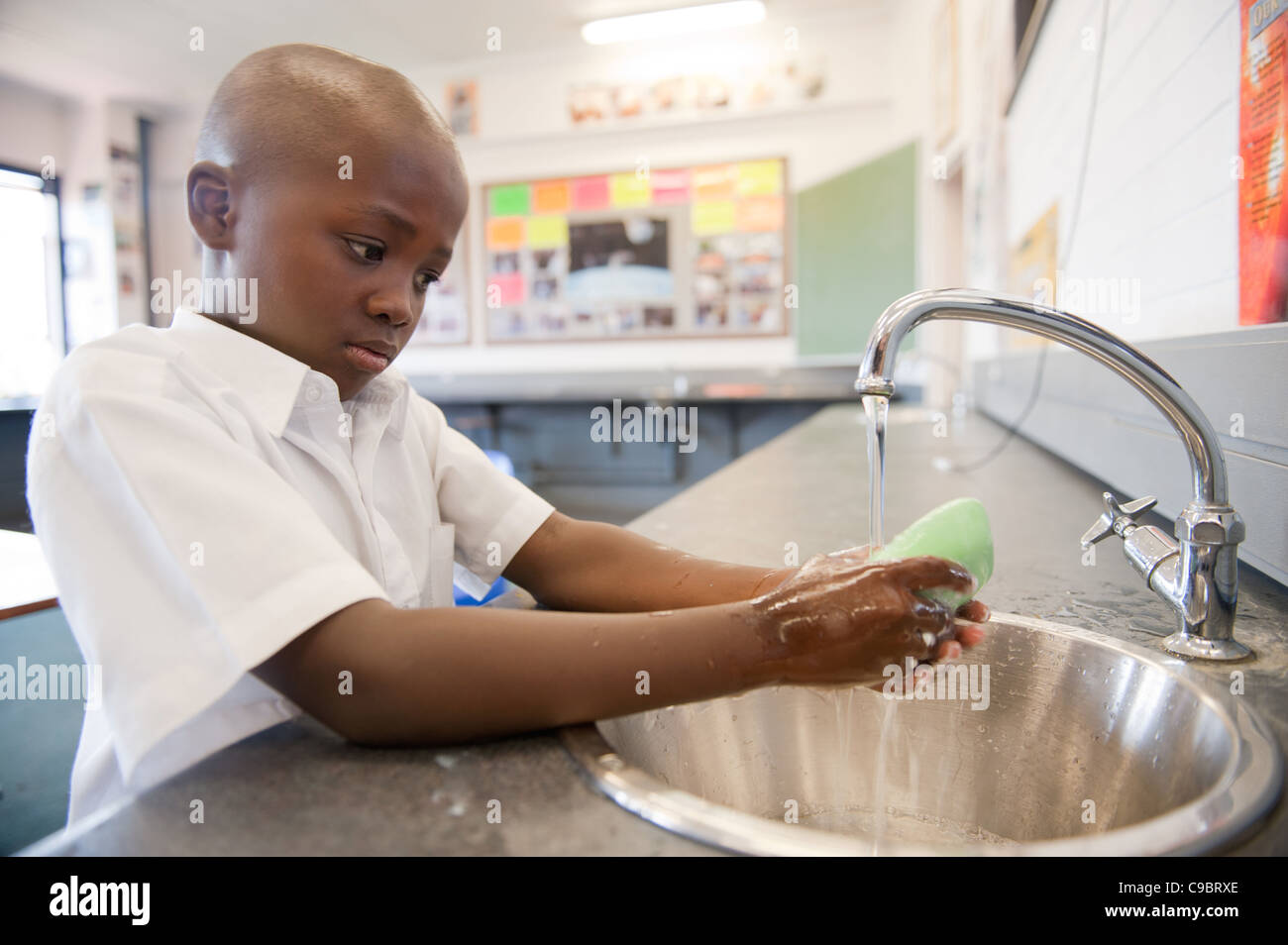 Boy washing hands with soap in classroom, Johannesburg, Gauteng Province, South Africa Stock Photo