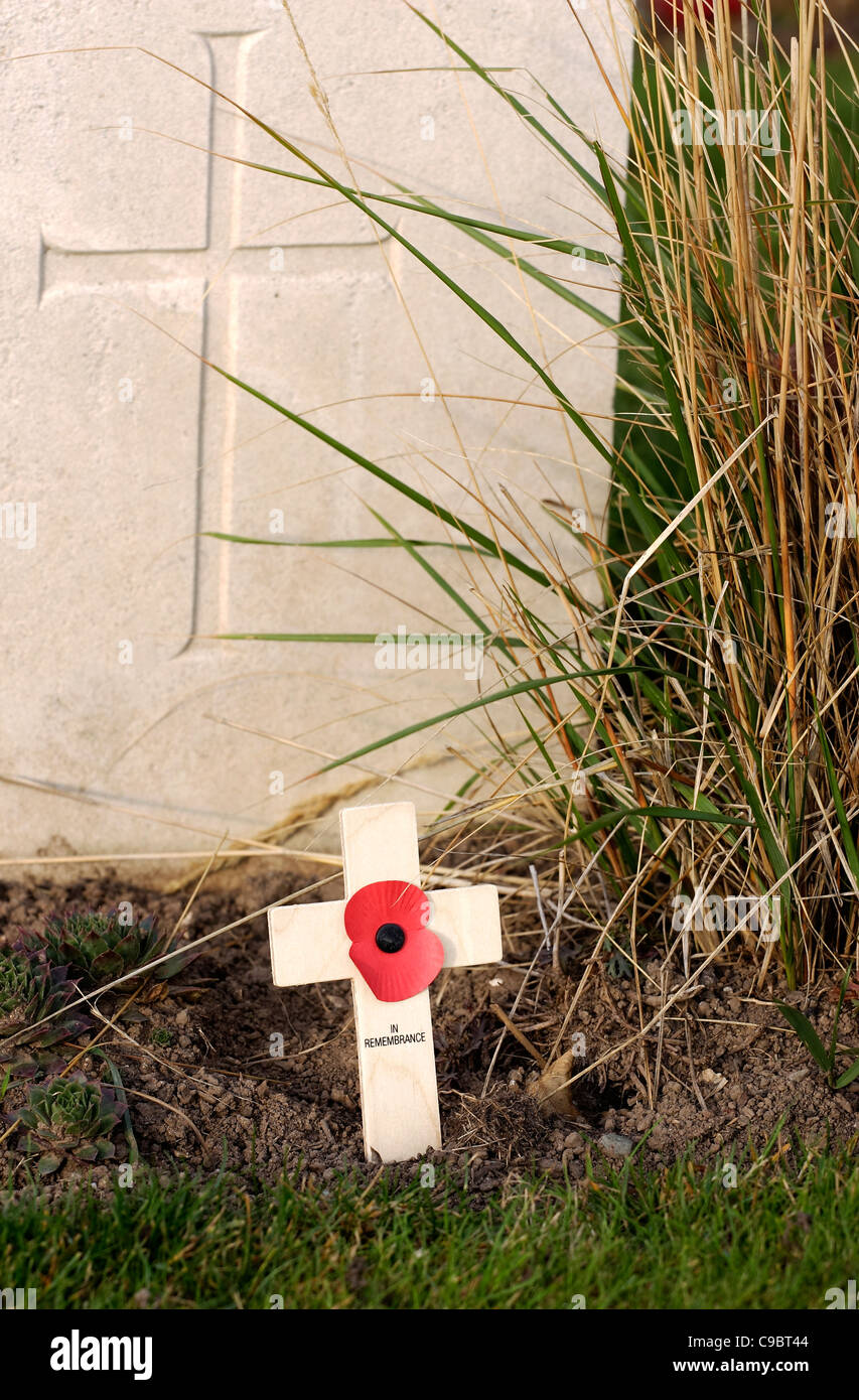 A military gravestone with a Remembrance Day cross and poppy in front as a mark of respect. - Stock Image