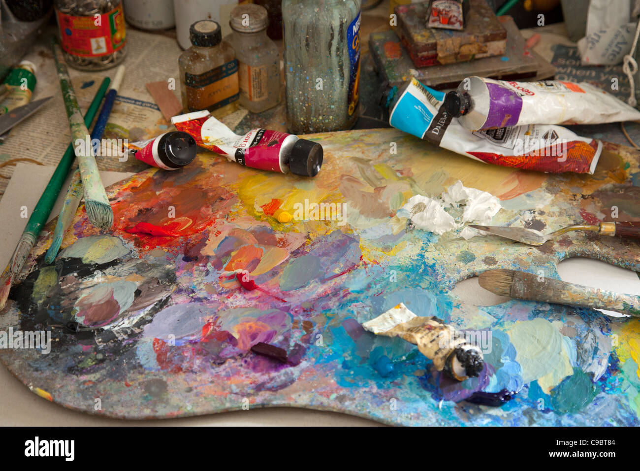 colorful artists Paint oil palette with brushes, knife, spatula, tube oils and jars. - Stock Image