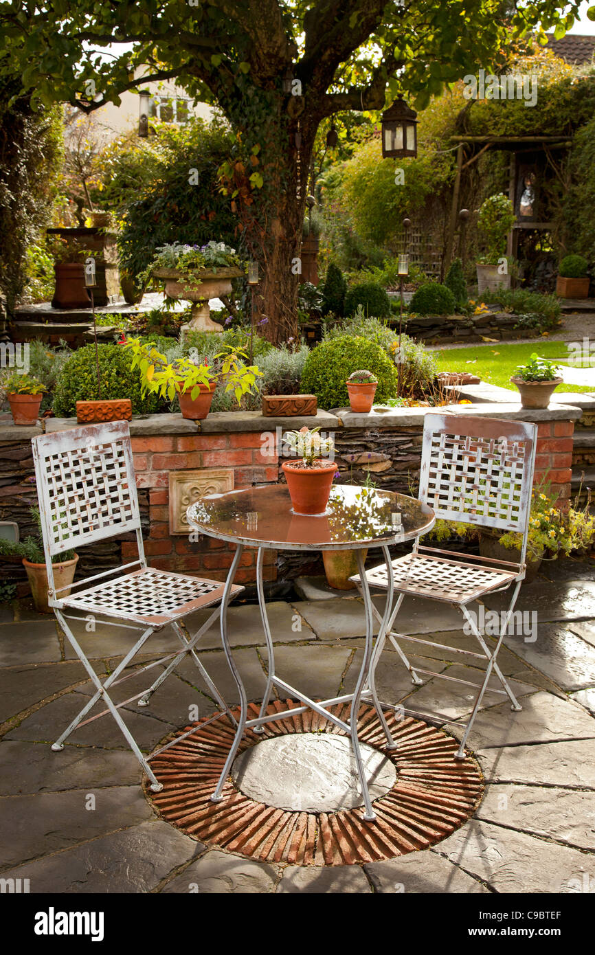 Metal table and chairs on stone patio in english autumn garden - Stock Image